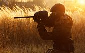 picture of paintball  - Paintball sport player in protective uniform and mask aiming gun before shooting at sunset - JPG