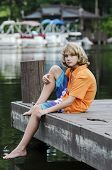 pic of dock a pond  - Young boy sitting on a dock in the bay - JPG
