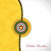 picture of rakhi  - Beautiful rakhi on floral decorated yellow and grey background for Happy Raksha Bandhan celebrations - JPG