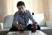 stock photo of alcohol abuse  - Attractive drunk business man at home sitting on couch at living room wasted holding whiskey bottle in alcoholism problem alcohol abuse and addiction concept looking grunge messy and sick with edgy radical studio lightning - JPG