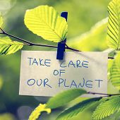 stock photo of take responsibility  - Take Care of our Planet concept with a handwritten note attached to a twig of fresh green sunlit leaves by a wooden clothes peg depicting the conservation of the ecology and natural resources - JPG