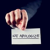 picture of apologize  - Businessman holding out a handwritten business card reading We Apologize in a concept of client service and public relations - JPG