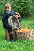 image of chanterelle mushroom  - Boy sitting near basket full of chanterelle mushrooms - JPG