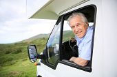 picture of motorhome  - Senior man in motorhome sitting by steering wheel - JPG