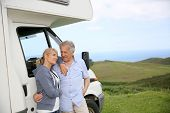 image of motorhome  - Senior couple standing by motorhome in countryside - JPG