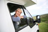 foto of motorhome  - Happy senior woman by motorhome window - JPG