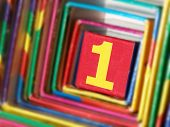 pic of oblique  - The number 1 in red and yellow on a cube in a colorful surround viewed close up at an oblique angle - JPG