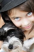 stock photo of snuggle  - Young girl looking directly into the camera wearing a fashionable black hat and snuggling her puppy. Extreme shallow depth of field with selective focus on eyes.