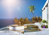 pic of beachfront  - Modern tropical outdoor patio overlooking the sea with built in seating and palm trees under a hot summer sun in a clear blue sky - JPG