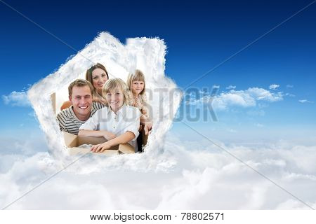 Loving family packing boxes against bright blue sky over clouds
