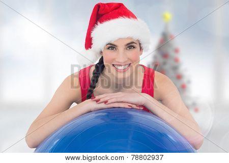 Festive fit brunette leaning on exercise ball against blurry christmas tree in room