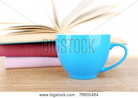 Cup of coffee and open book on wooden surface isolated on white