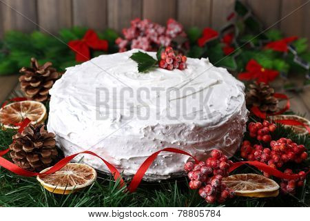 Christmas cake with wreath on wooden background