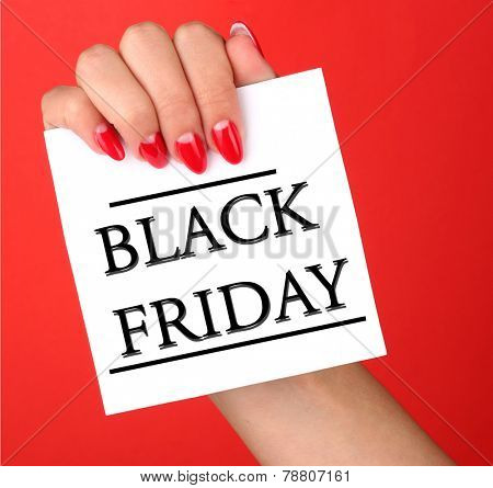 Woman's hand holding card with Black Friday text on red background