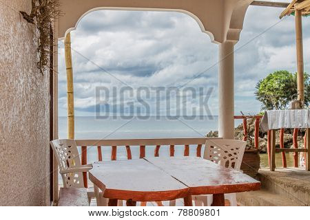 table in small outdoor cafe on tropical sea and sky background
