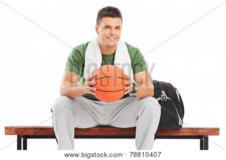 Young man with basketball sitting on a bench isolated on white background
