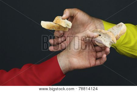 Two Men's Hands With Two Peaces Of A White Bread