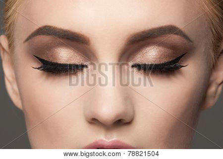 Closeup image of woman closed eyes with beautiful bright makeup.