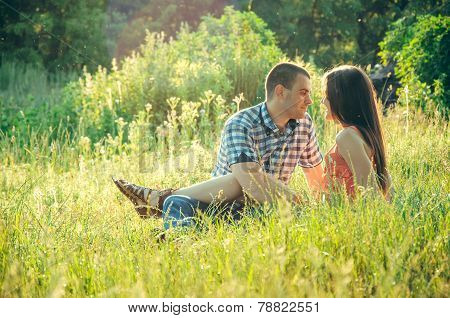 Couple Of Young Lovers Sitting On The Grass