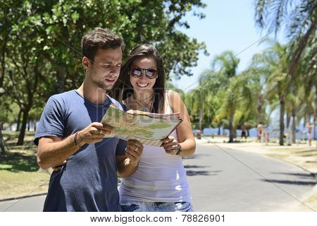 Happy tourist couple with map doing sightseeing with copy space