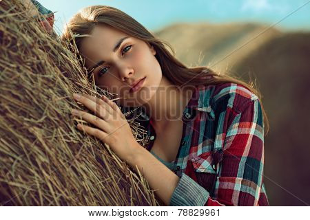 Girl Rests Against Haystack