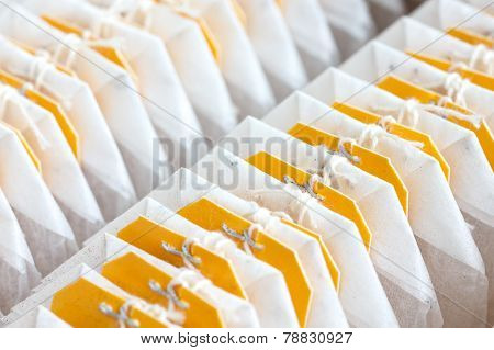 Yellow tagged teabags packed in a row.