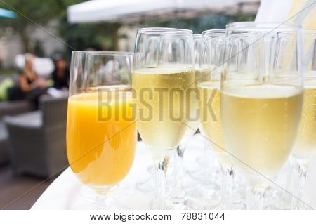 Waiter holding tray of champagne outside. Detail.