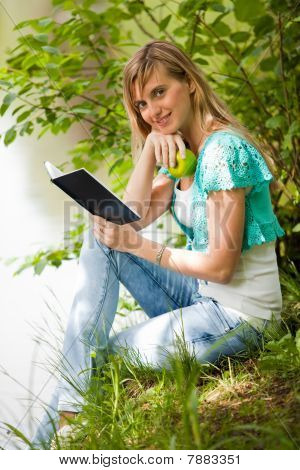 Young Woman Sits On A Grass In Park.