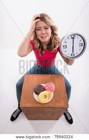 Time for diet slimming. Beautiful woman with clock keeps herself