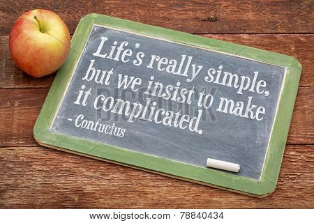 Life is really simply, but we insist to complicate it - a wisdom quote by Confucius on a slate blackboard against red barn wood