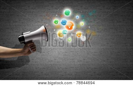 Close up of human hand holding megaphone