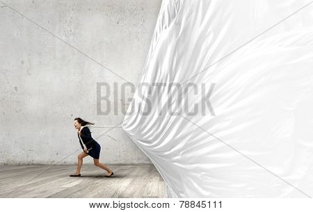 Young determined businesswoman pulling white blank banner with rope