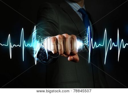 Close up of businessman grasping cardiograph in fist