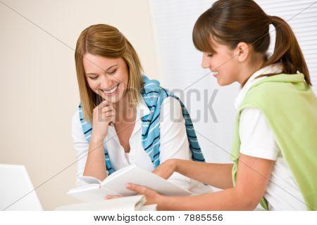 Estudiante en casa - dos mujeres con libro y portátil