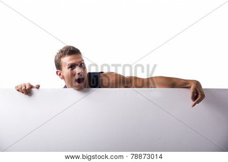 Strong Muscular Young Man Behind A Blank Horizontal White Banner