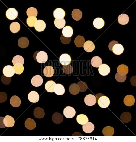 Golden bokeh on a dark background. Defocused bokeh lignts. Abstract Christmas background. Abstract c
