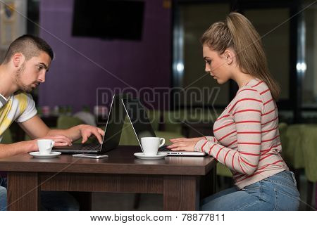 Smiling Young Students In Cafe Using Laptop