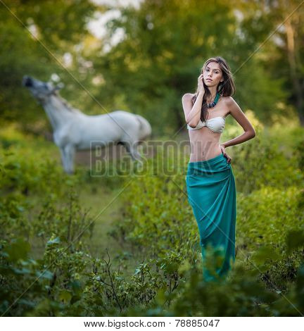 Young women in a blue long skirt and white bra at sunset in forest with a white horse in background