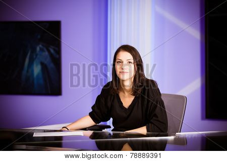 Young beautiful television announcer at studio during live broadcasting.