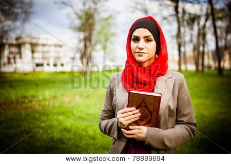 Beautiful muslim woman wearing hijab and holding the Koran