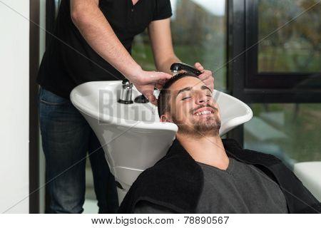 Hairdresser Washing Man Head In Barber Shop
