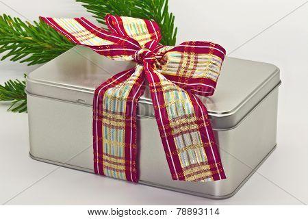 Tin box tied with ribbon.