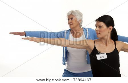 Yoga instructor coaching senior woman on white background