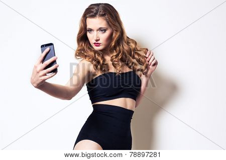 Pretty, young woman taking taking a selfie quite seriously and posing for it as a fashion model in front of white wall, making faces, playing with her hair, looking hot  portrait with her smart phone