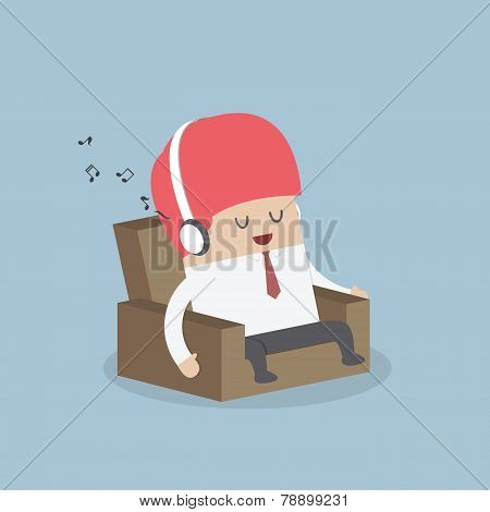 Businessman Relaxing On Sofa And Listening To His Headphones