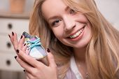 stock photo of expecting baby  - Closeup portrait of young attractive happy Caucasian woman with long fair hair holding cute baby shoe sitting in armchair - JPG