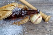 stock photo of baseball bat  - Close up of a brown bottled beer with crushed ice inside of baseball glove on rustic wood with ball and bat - JPG