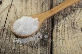 stock photo of crystal salt  - Wood spoon full with salt crystals on old brown wood table - JPG