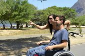 picture of disability  - Disabled man in wheelchair and girlfriend in the park - JPG