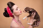 stock photo of headband  - Portrait of pretty brunette  girl in rose dress and red headband   in retro style  kissing  cute Chihuahua puppy on beige background - JPG